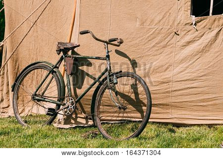 The Old Rarity Bicycle Parked Next To The Large Soviet Military Canvas Khaki Tent On Green Grass In Sunny Summer Forest.