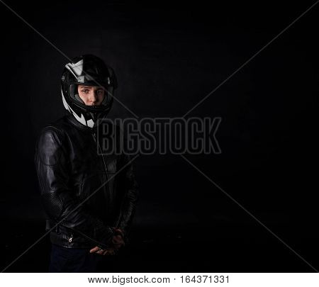 Man moto rider portrait on black background. Sport and extreme boy in motocycle equipment and helmet. Copy space for advertising text or biker goods.