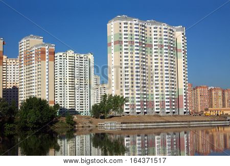 Landscape with constructed buildings in new city district after river over clear blue cloudless sky in summer day
