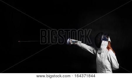 fencing player making blow on black background. Sport concept with free space for advertising text.