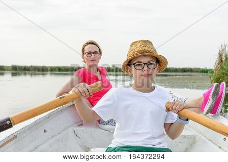 Cute Boy Paddling With Mother In Boat. Active Happy Boy Having Fun With Paddling Over Lake With Moth