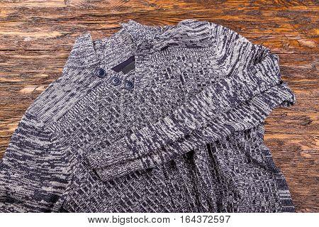warm gray melange men's winter sweater on a wooden background