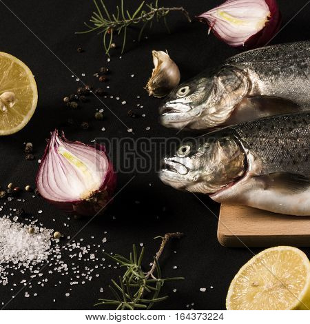 Two raw trouts with different ingredients on dark background.