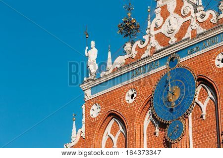Sculptures On The Facade Of  The House Of Blackheads In Riga, Latvia. Famous Landmark. Travel Destination. Town Hall Square. Four Statues Named After Neptune, Agreement, Peace, Mercury. Astronomical Clock and emblems