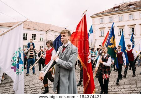 Vilnius, Lithuania - July 6, 2016: People dressed in traditional costumes take part in ceremonial procession with flags on Statehood Day. Holiday in commemorate coronation in 1253 of Mindaugas King.
