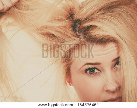 Hair care mistakes bleaching problems concept. Blonde woman holding her dry damaged hair.