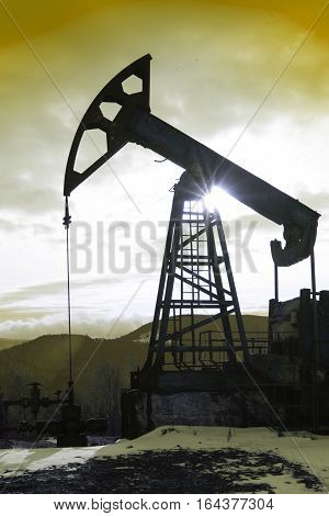 The oil pump industrial equipment. Oil rig sunset. Oil pumps on the sunset sky in winter mountains background. Oil industry equipment.