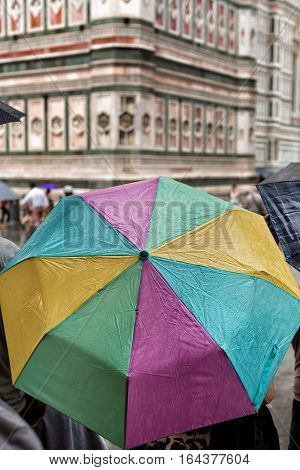 Tourists Shelter Beneath Colorful Umbrellas