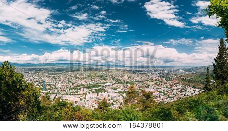 Panorama Of Tbilisi, Georgia. Aerial View Of Georgian Capital With Famous Landmarks: Justice House, Music Theatre And Sameba Holy Trinity Cathedral. Cityscape In Summer Sunny Day Under Blue Cloudy Sky.