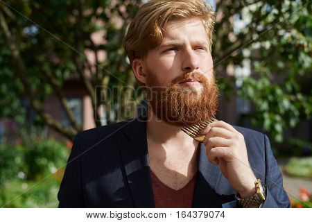 Red bearded hipster in summer time walking and comb out his beard.