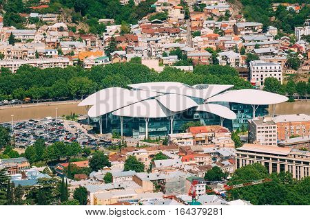 Tbilisi, Georgia. Aerial View Of Justice House, Public Service Hall The Fufuturistic Building With White Bizarre Roof At The Bank Of The Kura River, Surrounded By Populous Residential Area In Sunny Summer Day.