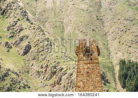 Ancient Old Stone Watchtower On Mountain Background In Sioni Village, Kazbegi District, Mtskheta-Mtianeti Region, Georgia. Spring Or Summer Season. Famous Landmarks And Places In Kazbegi District.