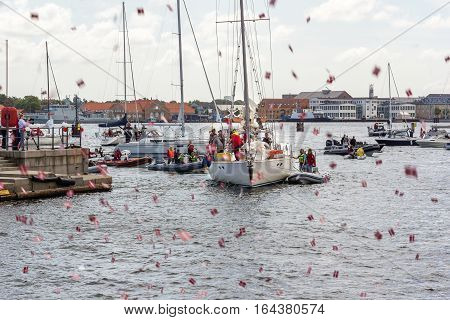 Copenhagen, Denmark, July 15, 2016 - People greeting popular danish salingboat after circumnavigation with shooting flags in the air.