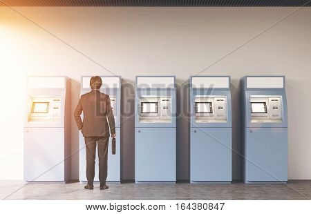 Rear View Of A Man Near Five Atm Machines