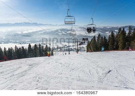 Czarna Gora Poland - December 30 2016: People go skiing on a sunny day with beautiful mountain view in the background.