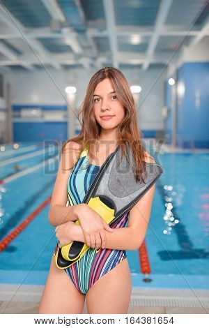 Young beautiful woman in swimsuit with flippers posing at swimming pool area.