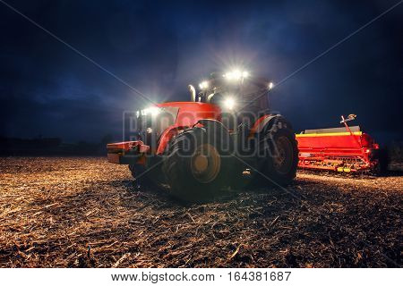 Tractor preparing land with seedbed cultivator at night