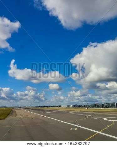 A Runway Under Puffy Clouds in Airport
