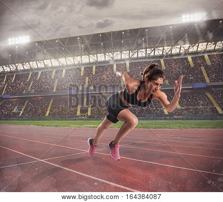 Athletic woman runs in a sport competition on the stadium track