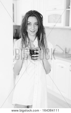 Sexy Brunette Woman In Kitchen Drinking A Cup Of Tea Or Coffee. Black And White Photo.