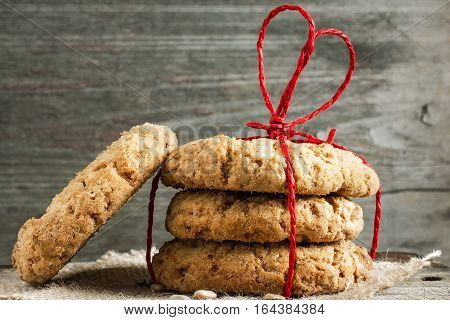 pile of oat cookies for Valentine's Day with red heart shaped ribbon on wooden table. valentines day background. close up