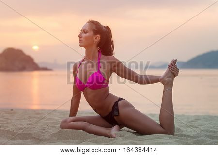 Young woman in pink bra and black panties sitting on beach stretching her legs during sunset at sea. Fitness girl doing exercises on seashore