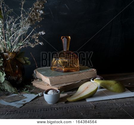 still life, vintage . old books, bouquet of flowers, pear, vase on a wooden table. dark backgrounds