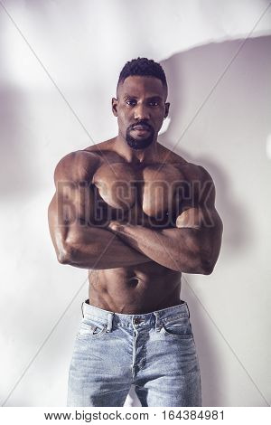 African American bodybuilder man, naked muscular torso, wearing jeans, on white background
