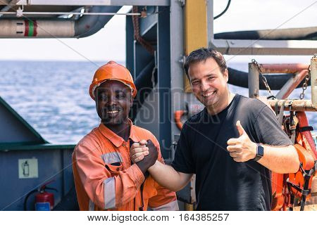 friendship of nations on board of ship/vessel. African seaman and European Chief Mate smiling and shaking hands on deck.