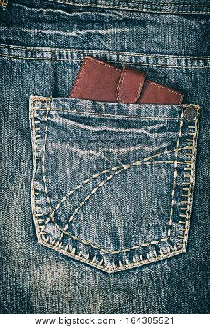 Leather brown wallet in the back pocket of jeans close-up vintage toning