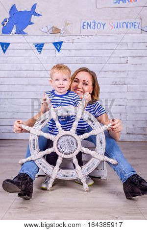 Happy baby and her mother in sailor T-shirts playing with steering wheel indoors. Travel and adventure concept. Studio shoot