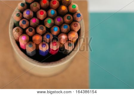 Multicolored pensils in the box on a blue background. Back to school. Copy space. Top view.
