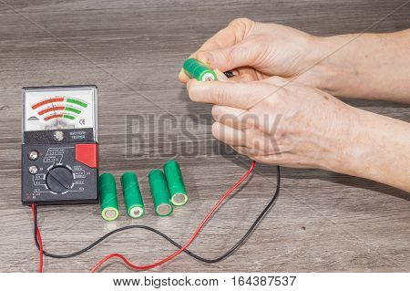 Person checking battery status with battery tester