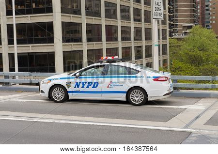 NEW YORK - APRIL 29 2016: NYPD police car posting at the beginning of the Brooklyn bridge