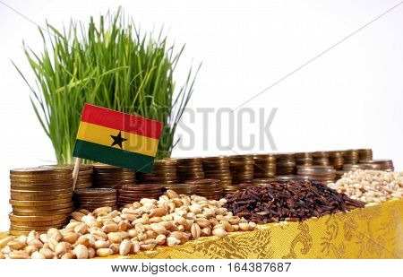Ghana Flag Waving With Stack Of Money Coins And Piles Of Wheat And Rice Seeds