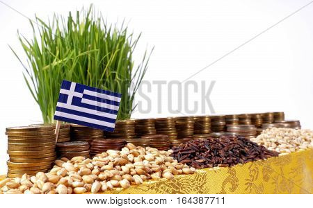 Greece Flag Waving With Stack Of Money Coins And Piles Of Wheat And Rice Seeds