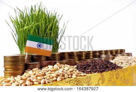 India Flag Waving With Stack Of Money Coins And Piles Of Wheat And Rice Seeds