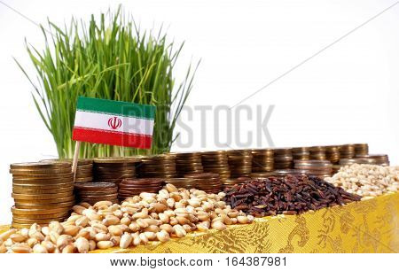 Iran Flag Waving With Stack Of Money Coins And Piles Of Wheat And Rice Seeds