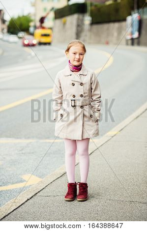 Outdoor portrait of young kid girl wearing beige trenchcoat and red boots