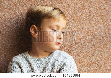 Handsome little 5-6 year old boy posing against brown background, wearing grey pullover