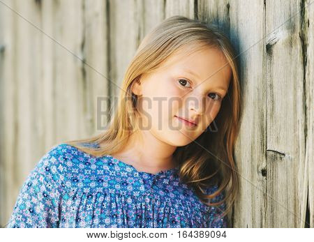 Close up portrait of a cute little girl of 8-9 years old wearing blue dress, leaning on old wooden wall