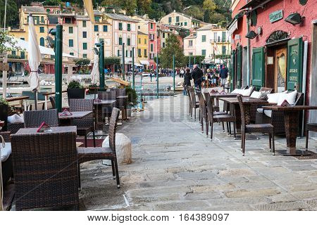 PORTOFINO, ITALY - DECEMBER 2016: Chairs and tables of Italian cafe at coast of Portofino town, Liguria, Italy