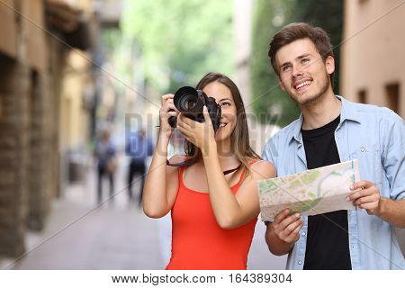 Joyful couple of tourists male and female photographing landmarks with a dslr camera in the street of an old town