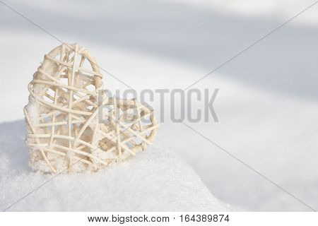 Vintage rattan heart on a white snow winter background. Love and Valentines Day concept.