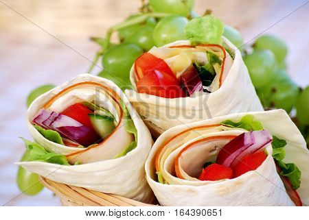 Ham and cheese wrap sandwiches in picnic basekt