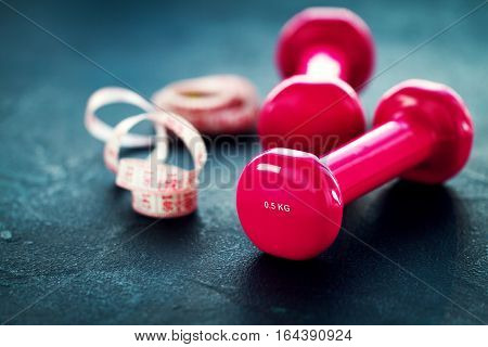 Pair of pink fitness dumbbells with centimeter ribbon on dark background. Horizontal with copy space.