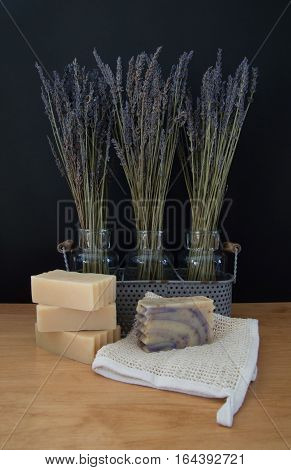 Three glass vases in a metal basket with sprigs of dried lavender against a black background with four bars of goats milk soap and a ramie washcloth in the foreground on a light wood table.
