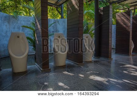 modern restroom with urinal row in the garden.