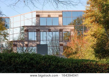 modern commercial and professional building portrait reflecting trees for commercial real estate