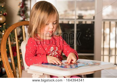 Young female baby girl in high chair making a jigsaw on a plastic tray at Christmas with tree in background